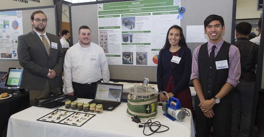 Four students stand in front of a poster explaining their Innovate to Grow capstone project.