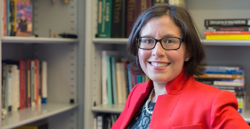 Professor Susana Ramirez in a red jacket and black-rimmed glasses stands in front of bookshelves filled with books.