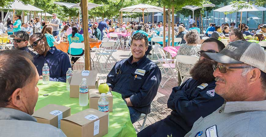 Several hundred UC Merced staff members, seated at tables outdoors, enjoy lunch during Staff Appreciation Week.